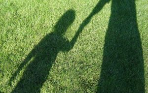 adult_and_child_shadows_on_grass_nr